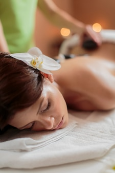 Giovane donna che ha una terapia di massaggio con pietre calde
