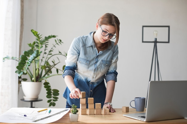 Giovane donna che impila blocco di legno sullo scrittorio del lavoro all'ufficio