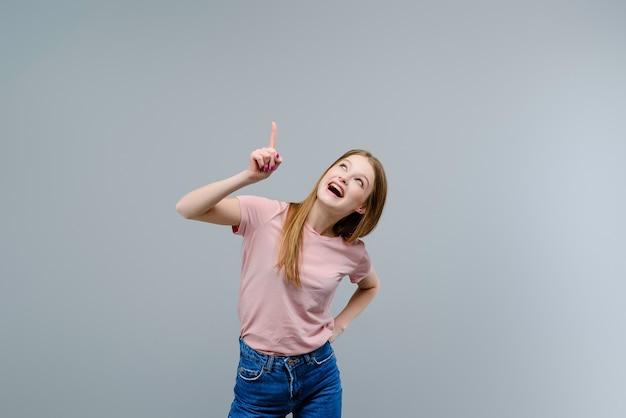 Giovane donna che indica in su allo spazio della copia isolato sopra priorità bassa grigia