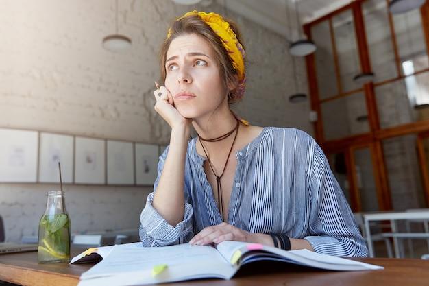 Giovane donna che indossa bandana e studia nella caffetteria
