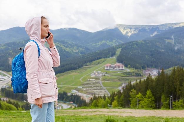 Giovane donna che indossa giacca e zaino blu, comunicando con il cellulare in cima alla montagna
