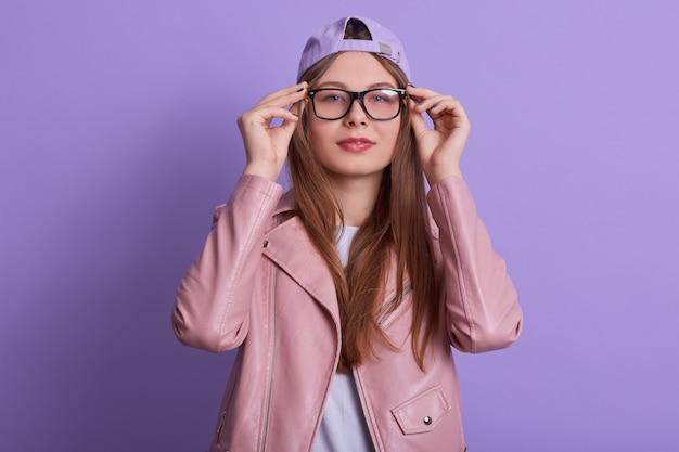 Giovane donna che indossa giacca rosa, cappello e occhiali