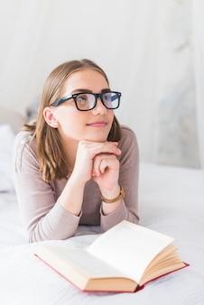 Giovane donna che indossa gli occhiali neri che fantasticano mentre leggendo libro sul letto