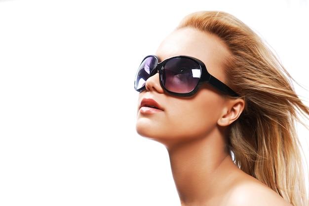 Giovane donna che indossa i grandi occhiali da sole moderni.
