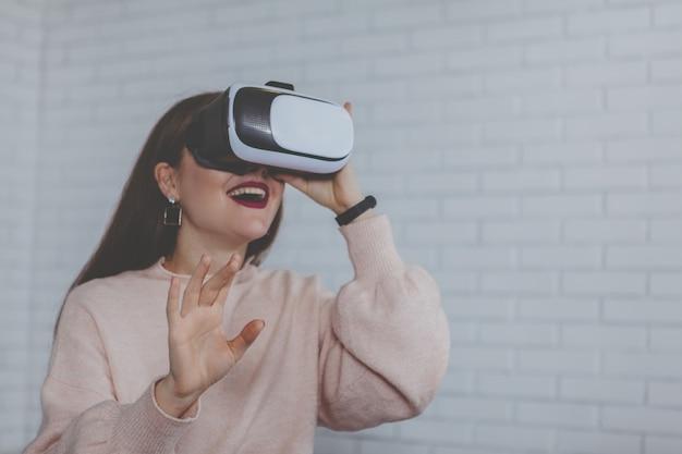Giovane donna che indossa i vetri di realtà virtuale 3d