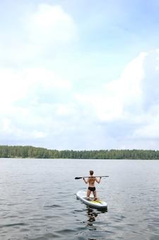 Giovane donna che indossa il costume da bagno nero nuotare nel lago su una tavola di sup.