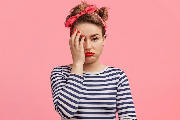 Giovane donna che indossa la fascia rossa e camicia a righe