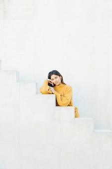 Giovane donna che indossa la felpa che si appoggia sui gradini