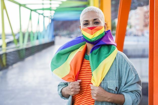 Giovane donna che indossa la maschera del gay pride, bandiera all'aperto - diritti lgbt, diversità, tolleranza e concetto di identità di genere