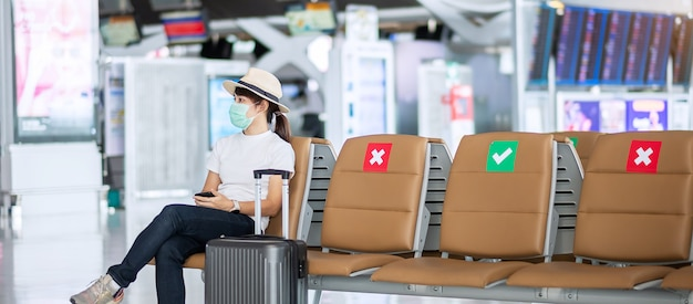 Giovane donna che indossa la maschera per il viso e seduta su una sedia in aeroporto, protezione dalla malattia da coronavirus (covid-19), viaggiatrice asiatica. new normal, bolla di viaggio e allontanamento sociale
