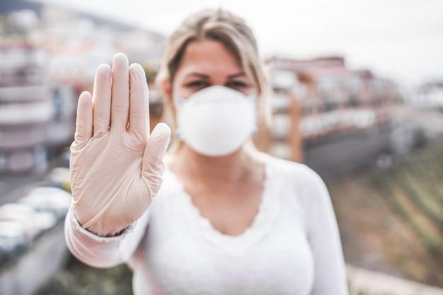 Giovane donna che indossa maschera e guanti in lattice mentre mostra il gesto della mano di arresto per la prevenzione del coronavirus - smetti di diffondere il concetto di covid 19 - concentrati sulla mano