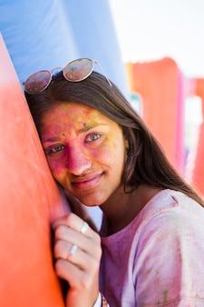Giovane donna che indossa occhiali da sole con il viso coperto di colore holi rivolto verso l'obiettivo