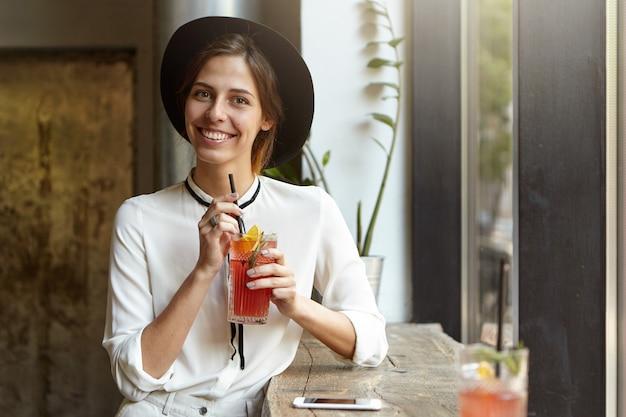 Giovane donna che indossa un grande cappello nella caffetteria