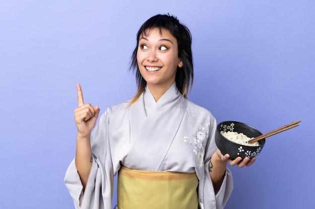 Giovane donna che indossa un kimono sul muro blu con l'intenzione di realizzare la soluzione sollevando un dito mentre si tiene una scodella di noodles con le bacchette