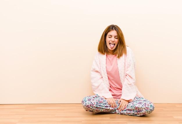 Giovane donna che indossa un pigiama seduto a casa con atteggiamento allegro, spensierato, ribelle, scherzando e tirando fuori la lingua, divertendosi