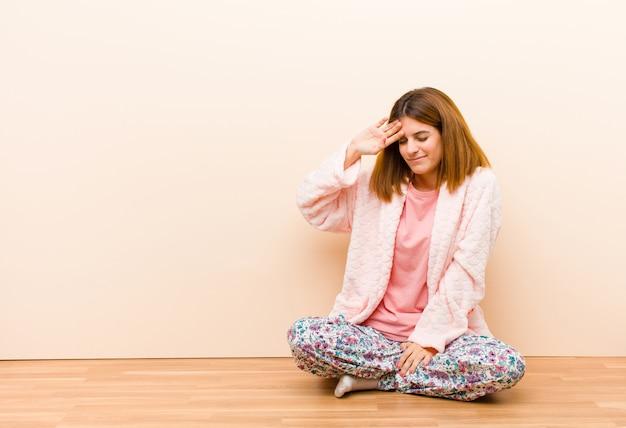 Giovane donna che indossa un pigiama seduto a casa guardando stressato, stanco e frustrato, asciugando il sudore dalla fronte, sentendosi senza speranza ed esausto