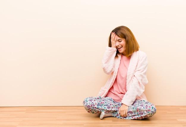 """Giovane donna che indossa un pigiama seduto a casa ridendo e schiaffeggiandosi la fronte come dire dâ € šãƒâ """"ãƒâ´oh! ho dimenticato o è stato un errore stupido"""