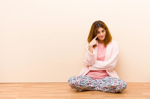 Giovane donna che indossa un pigiama seduto a casa tenendoti d'occhio, non fidandoti, guardando e rimanendo vigile e vigile