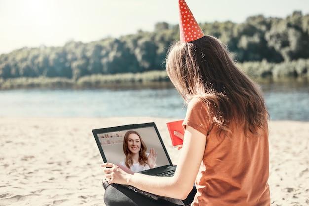 Giovane donna che indossa una maschera medica si siede sulla spiaggia con un computer portatile
