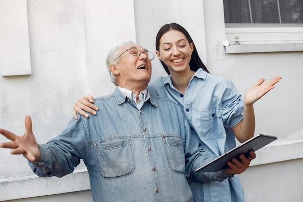 Giovane donna che insegna a suo nonno come usare un tablet