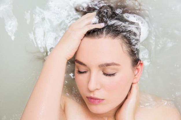 Giovane donna che lava i capelli. shampoo e schiuma sui capelli della donna nera.