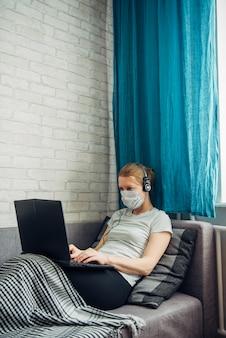 Giovane donna che lavora a casa durante la quarantena. donna malata che indossa la maschera con il computer portatile, sdraiato sul divano. ufficio remoto, concetto di autoisolamento