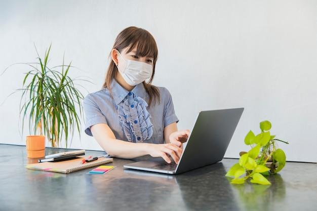 Giovane donna che lavora a casa e usando una maschera