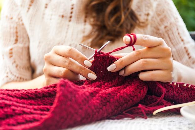 Giovane donna che lavora a maglia sulla terrazza nella caffetteria