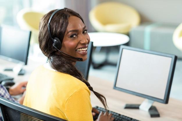 Giovane donna che lavora al computer con l'auricolare