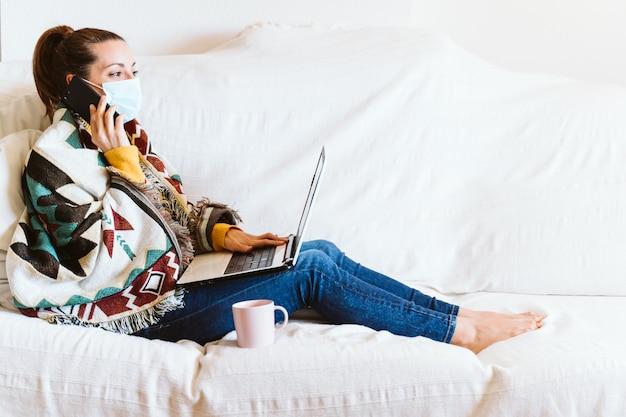 Giovane donna che lavora al computer portatile a casa, seduto sul divano, indossando una maschera protettiva. resta a casa durante il coronavirus covid-2019