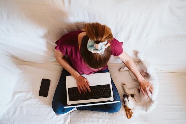 Giovane donna che lavora al computer portatile a casa, seduto sul divano, simpatico cagnolino inoltre. concetto di tecnologia e animali domestici