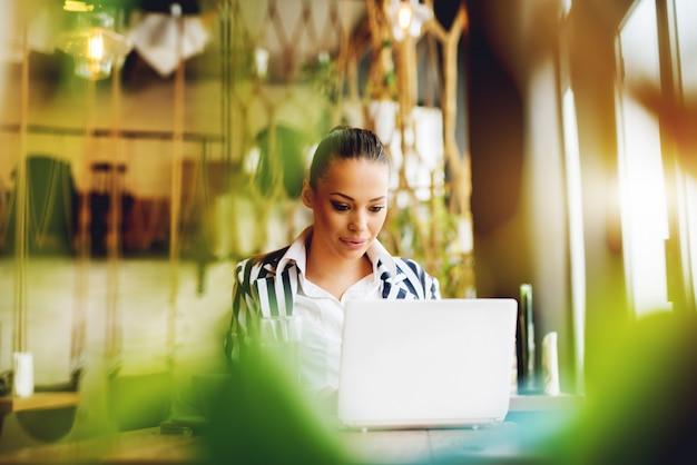 Giovane donna che lavora al computer portatile al bar caffetteria.
