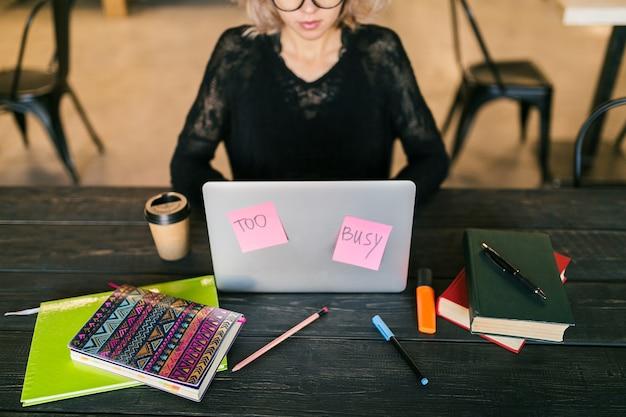 Giovane donna che lavora al computer portatile in ufficio di co-working