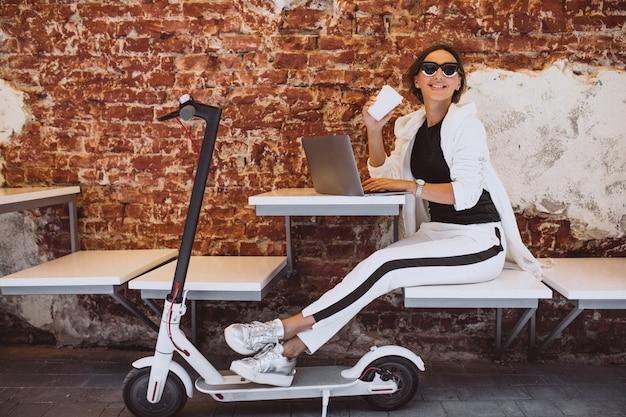 Giovane donna che lavora al computer portatile in un caffè