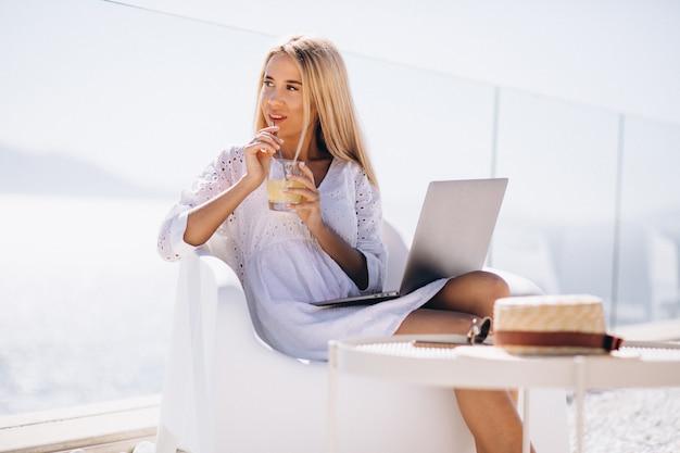 Giovane donna che lavora al computer portatile in vacanza