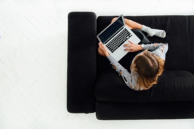 Giovane donna che lavora al computer portatile, seduto sul divano accogliente nero, pavimento bianco.