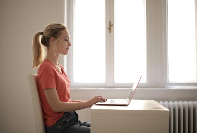 Giovane donna che lavora al suo laptop su un tavolo in una stanza