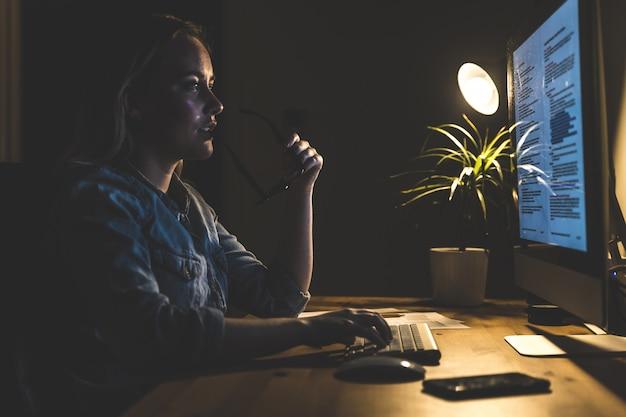 Giovane donna che lavora alla stazione di computer a casa