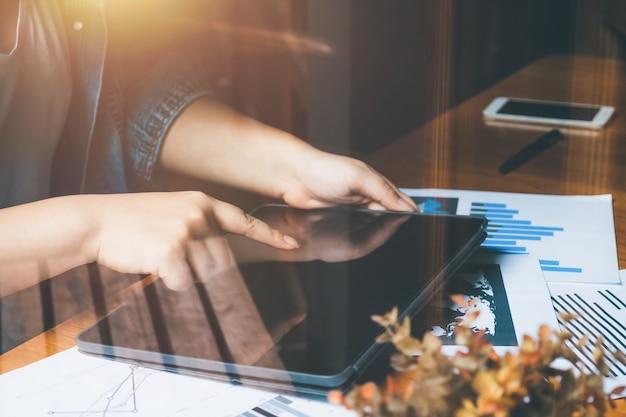 Giovane donna che lavora con documenti grafici e tablet touch screen a mano