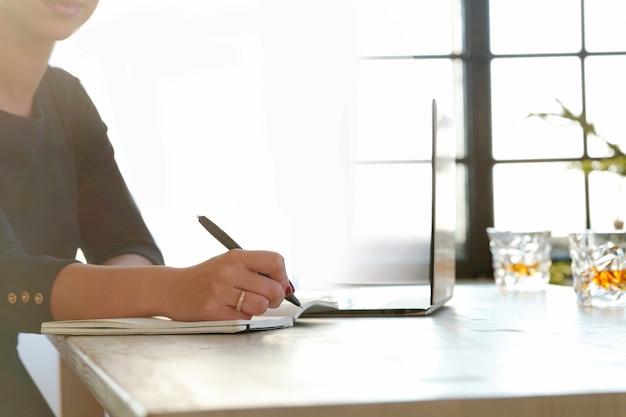 Giovane donna che lavora con il computer portatile e l'agenda