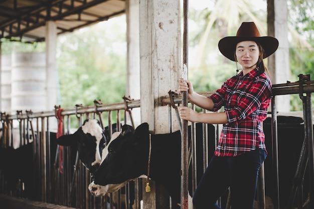 Giovane donna che lavora con il fieno per mucche in caseificio