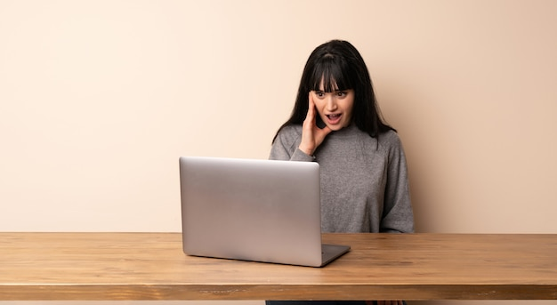 Giovane donna che lavora con il suo computer portatile con espressione facciale sorpresa e scioccata