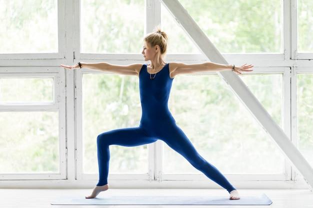 Giovane donna che lavora, facendo yoga o esercizio di pilates