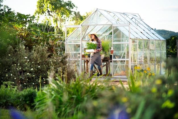 Giovane donna che lavora in una serra di vetro