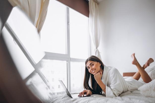 Giovane donna che lavora sul computer a letto