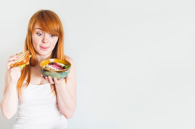 Giovane donna che lecca la sua lingua mentre guardando la ciotola di farina d'avena