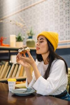 Giovane donna che lecca le labbra e che tiene dessert vicino alla tazza alla tavola