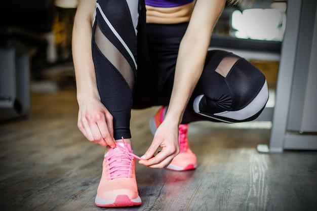 Giovane donna che lega i lacci delle scarpe prima dell'allenamento in palestra.