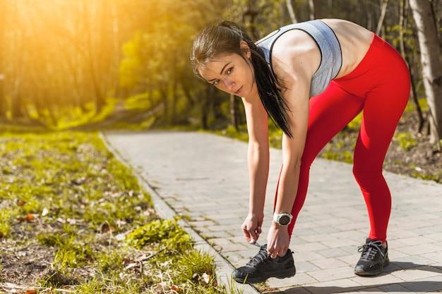 Giovane donna che lega la sua sneaker