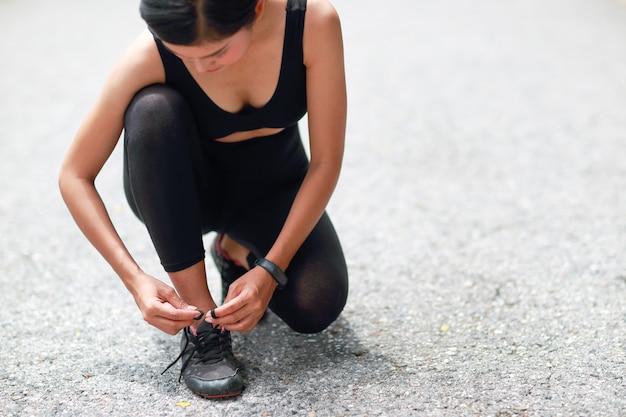 Giovane donna che lega le scarpe da corsa